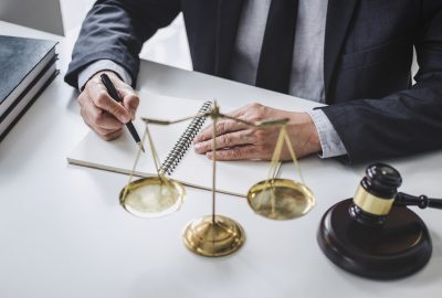 Male lawyer or judge working with contract papers, Law books and wooden gavel on table in courtroom, Justice lawyers at law firm, Law and Legal services concept.
