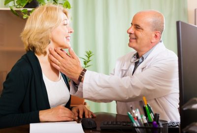 Mature doctor checking thyroid of smiling woman  in clinic
